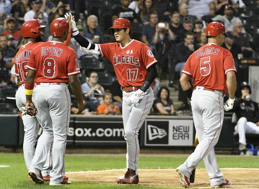The Angels' Shohei Ohtani is greeted by teammates after hitting a three-run homer Sept. 7, 2019.
