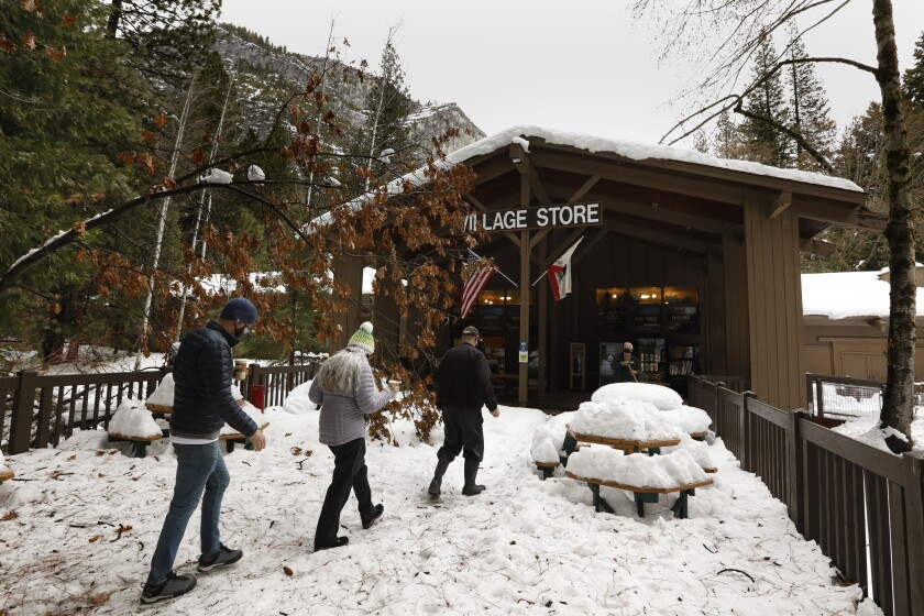 Yosemite Park employees walk through snow to the Village Store.
