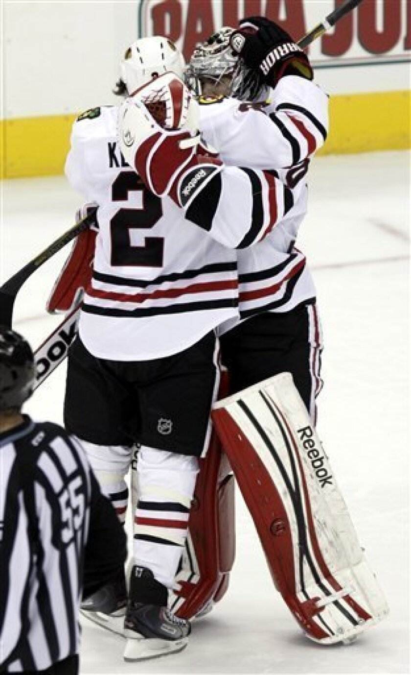 Chicago Blackhawks' Duncan Keith, left, celebrates with goalie Corey Crawford following the Blackhawks' 2-1 win over the Columbus Blue Jackets in a shootout during an NHL hockey game in Columbus, Ohio, Thursday, March 14, 2013. (AP Photo/Paul Vernon)