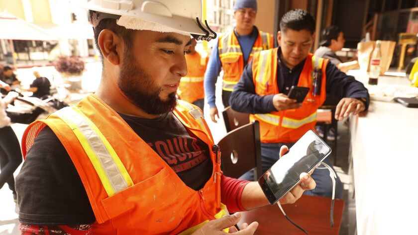 Christian Herrera, left, shows the alert message on his cell phone minutes following the 11:18 A.M. 'Presidential Alert' on Wednesday at Grand Central Market in downtown Los Angeles.