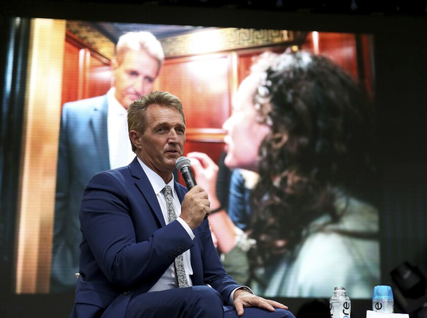 Sen. Jeff Flake, R-Ariz., speaks at the Forbes 30 Under 30 Summit in Boston, in front of a photo of him being confronted in an elevator Friday at the Capitol in Washington by two women who said they were sexual assault victims.