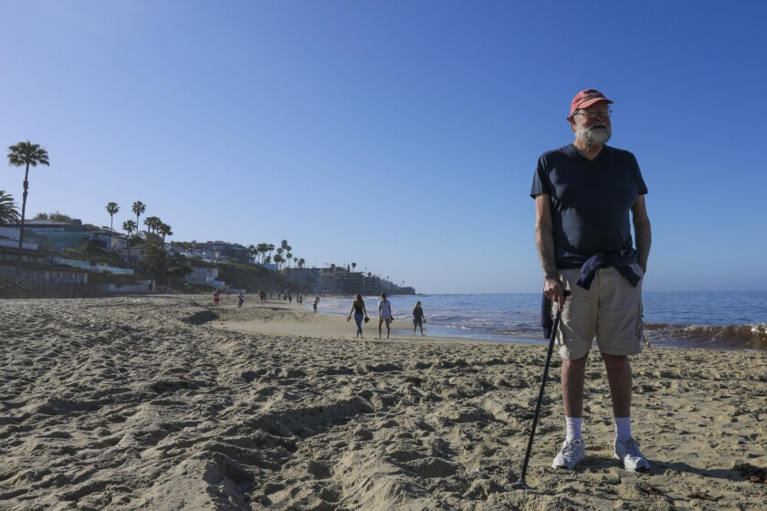 David Peck, 82, enjoys the view of the Laguna Beach shoreline Tuesday morning as the city reopened its beaches for active use.
