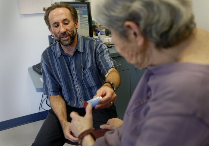 Patient Corinne Geller, right, talks with Dr. Martin Schulman, a concierge physician, about some of her medical issues, such as whether she is using the right inhaler.