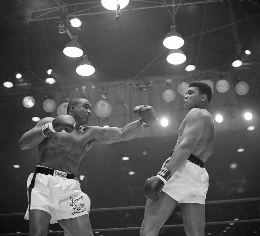 FILE - In this Feb. 26, 1964 file photo, Muhammad Ali (Cassius Clay)  uses a variety of bobbing and weaving to stay clear of the left arm of Sonny Liston in their title fight in Miami Beach, Fla.  Ali, the magnificent heavyweight champion whose fast fists and irrepressible personality transcended s