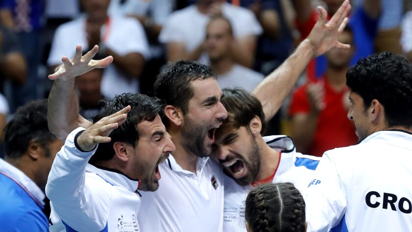 Marin Cilic (arms raised) celebrates Sunday with his Croatian teammates after clinching a spot in the Davis Cup final.