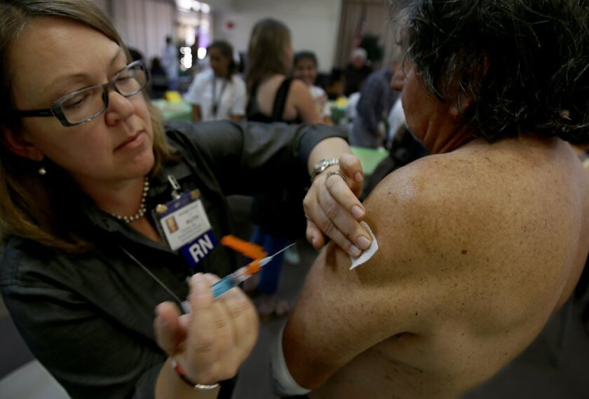 Nurse Ruth Pichaj administers a flu shot to Julio Hernandez on Tuesday. As the first flu death of the season was confirmed, L.A. County health officials urged everyone to get their flu vaccines.
