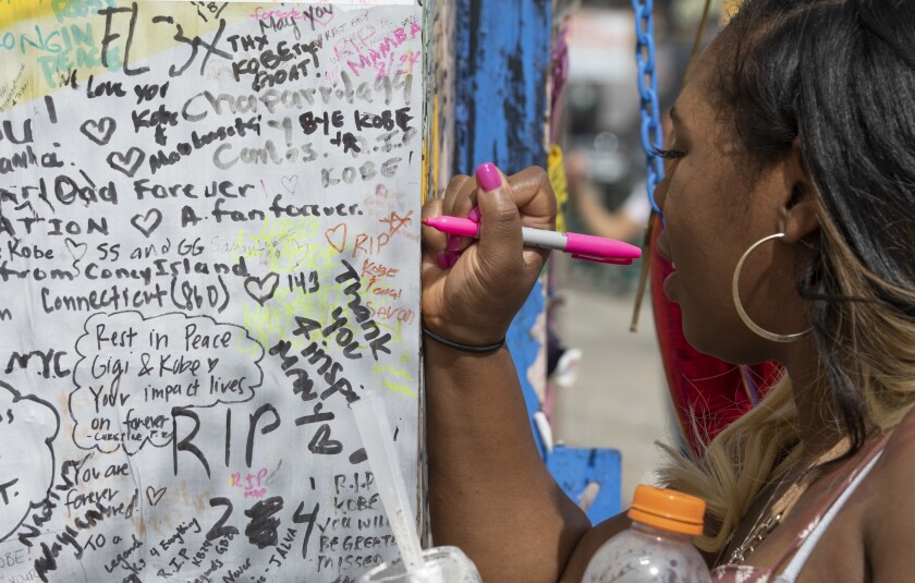 Diana Rutledge of Dayton, Ohio, writes a message on a mural on South La Brea honoring Kobe Bryant and his daughter Gianna