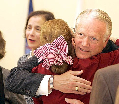 Hugs all around at the reception where Edward Blecksmith, father of Second Lt. James P. Blecksmith (mother Pamela in background), is greeted by attendees of a ceremony to rename the U.S. Marine Reserve Training Center in Pasadena in honor of their son.
