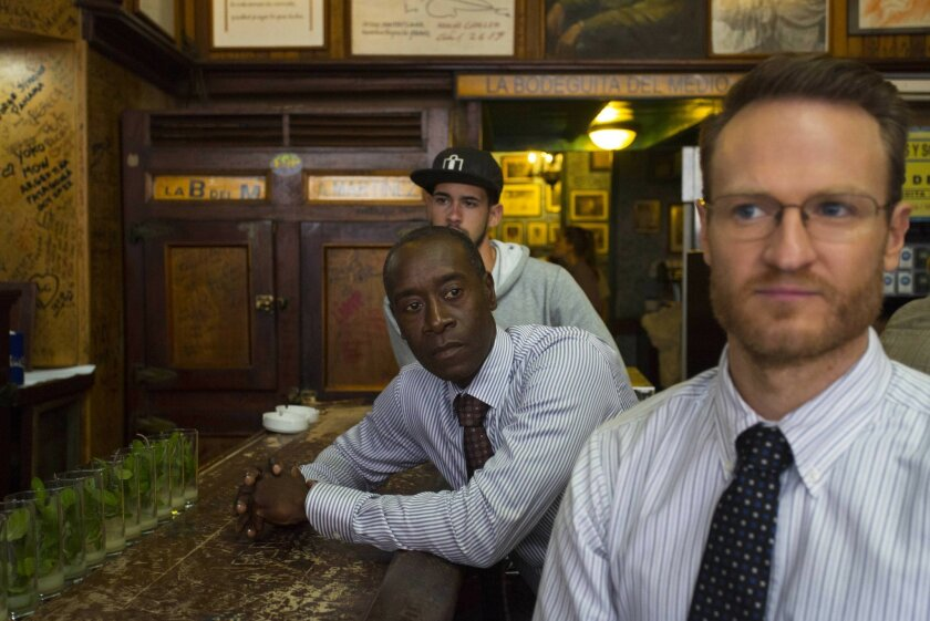"""In this Jan. 15, 2016 photo, """"House of Lies"""" actors Don Cheadle and Josh Lawson, right, sit at the bar counter in Bodeguita Del Medio during the filming of an episode, in Havana, Cuba. The producers of Showtime's dark comedy """"House of Lies"""" had $3 million and a mission: shoot the first episode of scripted American television in Cuba in more than half a century. (AP Photo/Desmond Boylan)"""