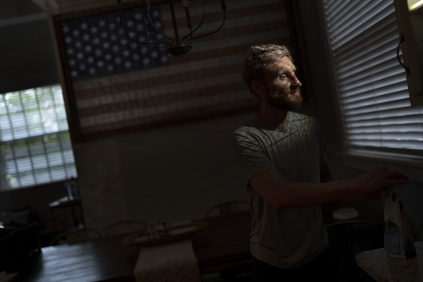Brad Snyder prepares tea for his wife in their kitchen decorated with a flag handcrafted by Brooklyn firefighters using recycled firehose, in Princeton, N.J., on Wednesday, Aug. 4, 2021. Losing his sight, he says, seems to matter more to other people. (AP Photo/Emilio Morenatti)