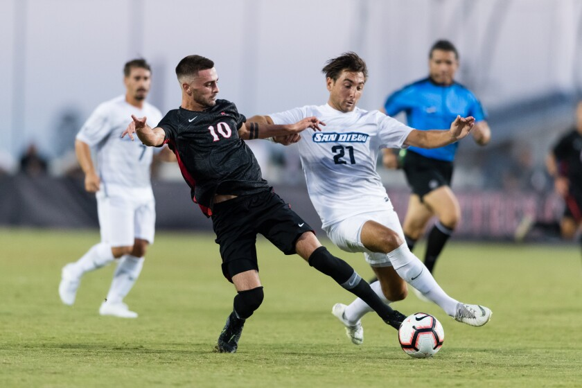 SDSU's Keegan Kelly tries to keep the ball from USD's George West in the Toreros' 3-2 win on the Sports Deck on Friday night.