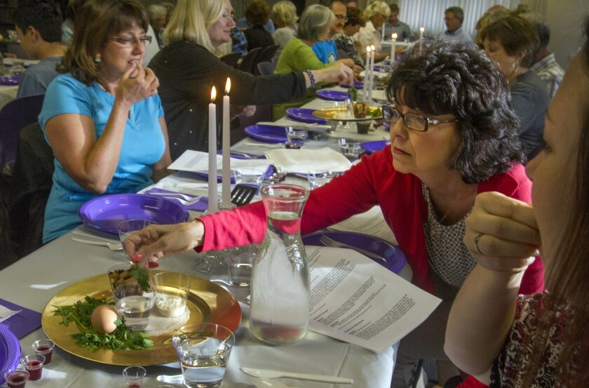 In remembrance of the suffering of Hebrew slaves Kathy Liggett, right, dips her green vegetable called Karpas into salt water during a ceremonial Passover dinner at the Christ Presbyterian Church in Carlsbad Thursday. photo by Bill Wechter