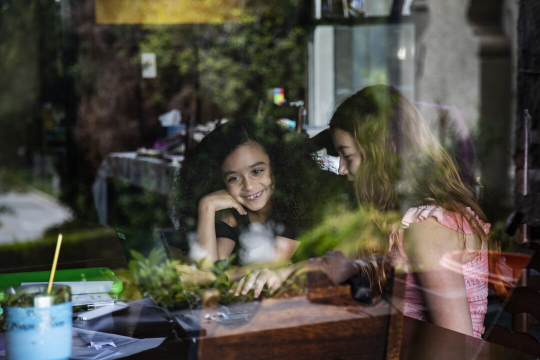 Allison Furbush, left, and Ellie Bristow are seen through a front porch window while teaming up on a science project.
