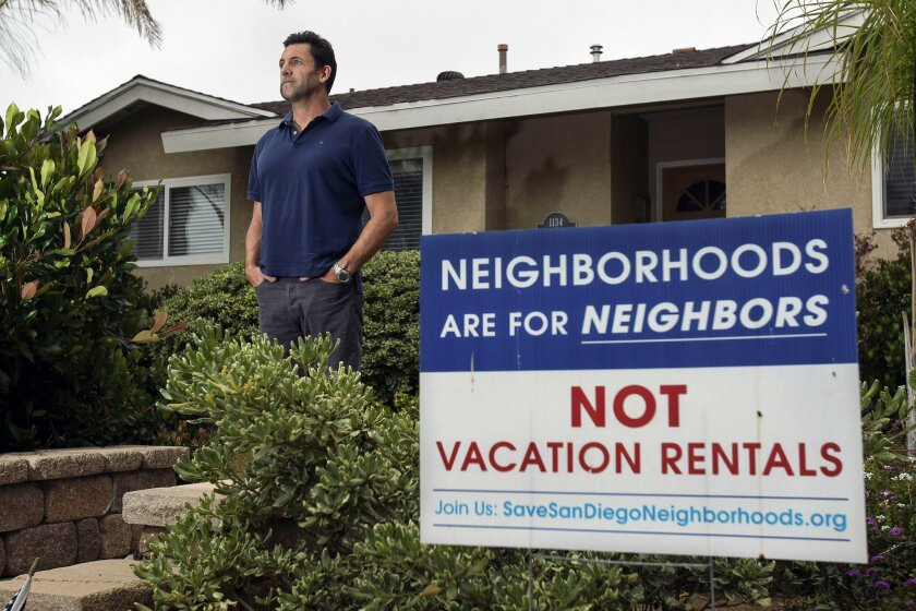 Ronan Gray, who says noise from a vacation rental next door has been a problem for him and his family, stands in front of his home in Pacific Beach. Gray is a co-founder of the Save San Diego Neighborhoods alliance fighting for more regulation of short-term rentals.