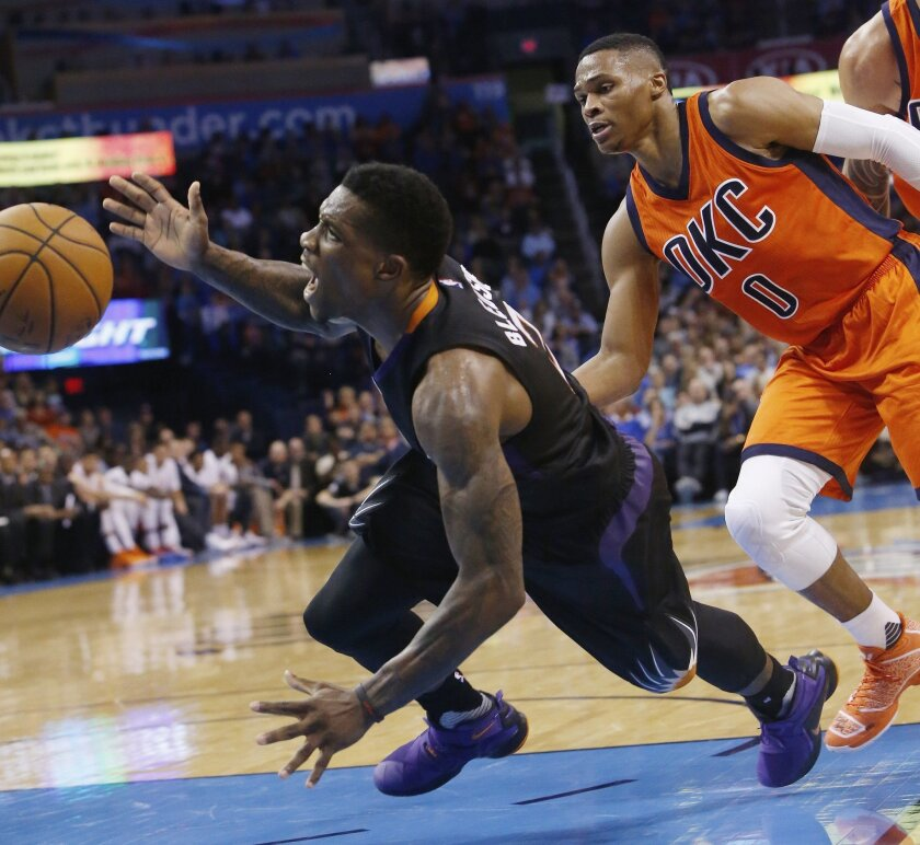 Phoenix Suns guard Eric Bledsoe (2) looses the ball as he fouled by Oklahoma City Thunder guard Russell Westbrook (0) in the second quarter of an NBA basketball game in Oklahoma City, Sunday, Nov. 8, 2015. (AP Photo/Sue Ogrocki)