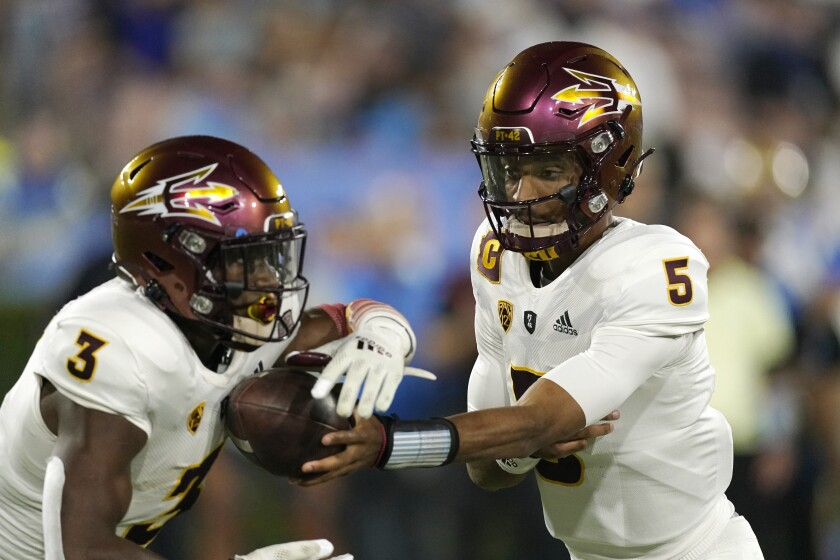 Arizona State quarterback Jayden Daniels, right, hands off to running back Rachaad White during the first half of an NCAA college football game against UCLA Saturday, Oct. 2, 2021, in Pasadena, Calif. (AP Photo/Mark J. Terrill)