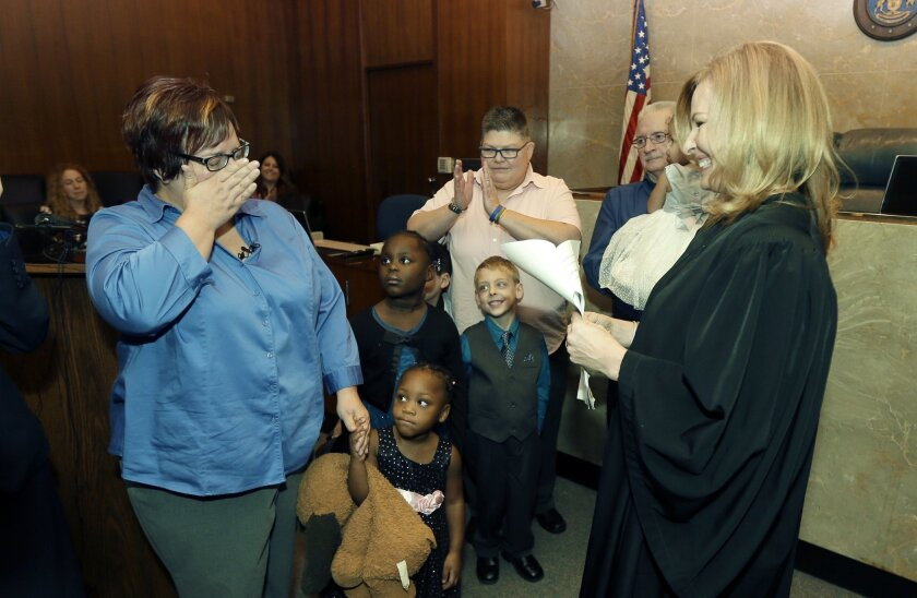 April DeBoer, left, wipes away tears before Judge Karen McDonald, right, and DeBoer's spouse Jayne Rowse, center, after an adoption ceremony at the Oakland County Circuit Court, Thursday, Nov. 5, 2015, in Pontiac, Mich. DeBoer and Rowse, the same-sex couple from Michigan has jointly adopted five ch