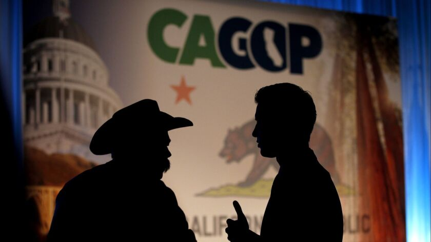 ANAHEIM, CALIF. -- FRIDAY, SEPTEMBER 18, 2015: Republican Party members are silhouetted talking bef