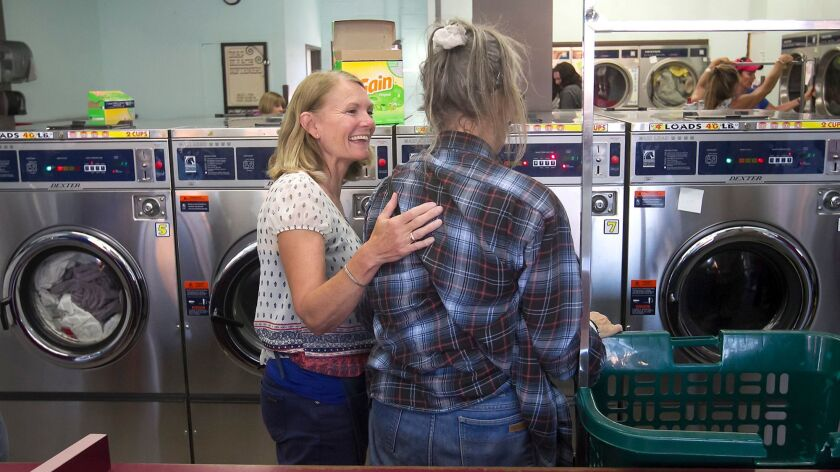 A volunteer with Laundry Love, left, greets a client who arrives at the washing machines with bags o