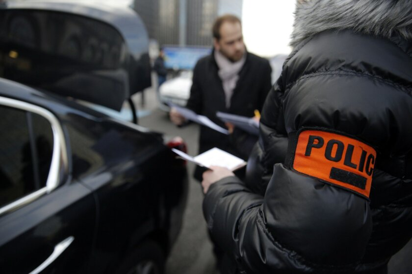 Plainclothes police officers check chauffeurs at the Paris' Gare de Lyon railway station, Thursday, Feb. 11, 2016. Chauffeurs claim they are victims of discrimination by the government, while taxi drivers complain for unfair competition from services such as Uber, during several protests in the rec