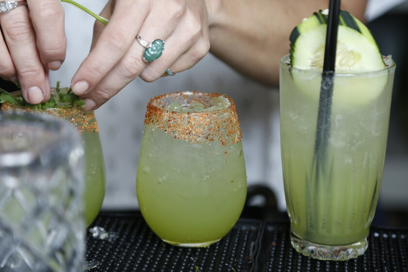 """Pacific Magazine Blind Daters Taylor and Neil ordered the """"2:15 to Cabo,"""" on the left, consisting of Sunday Gin, cucumber, honeydew shrub, Topo Chico, Tajin rim and garnished with cilantro and the """"Do you want that spicy?"""" made with Sunday Gin, grapefruit"""
