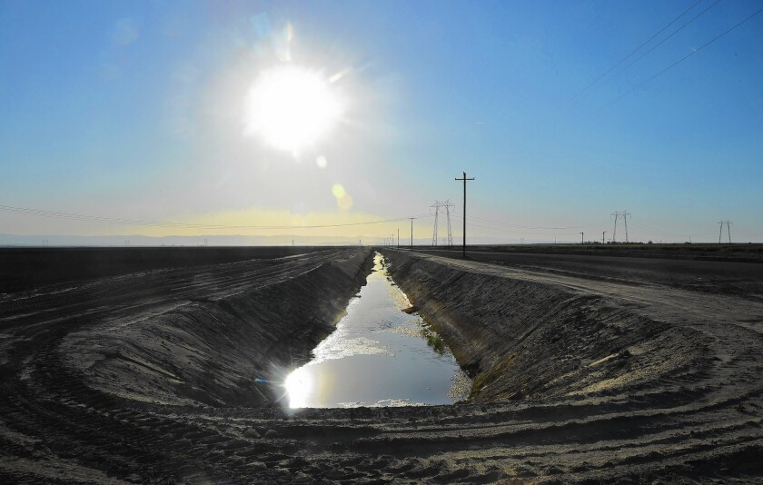 Water flows in an aqueduct amid crop fields in Kern County. The Central Valley produces more than $40 billion in crops each year, making California the biggest ag state in the U.S.