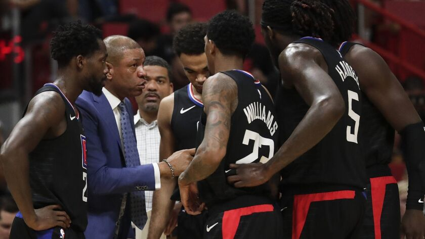 Coach Doc Rivers huddles with his players during a timeout Wednesday night in Miami.