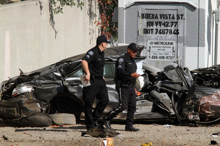 Two Burbank police officers walk past a car hit by a train at the intersection of San Fernando Boulevard and Buena Vista Street in Burbank.