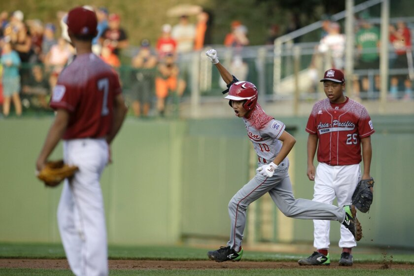 Japan's Shingo Tomita (10) celebrates after hitting a home run off Taiwan's Wei Hung Chou (7) as Yen Cheng Yu (25) watches during the first inning of an international pool play baseball game at the Little League World Series, Friday, Aug. 21, 2015, in South Williamsport, Pa. Japan won 7-5. (AP Photo/Matt Slocum)