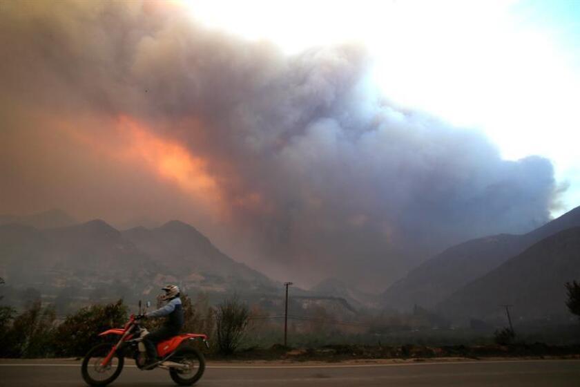 Un motociclista pasa frente a un área afectada por el incendio Thomas en Ojai (EE.UU.). EFE