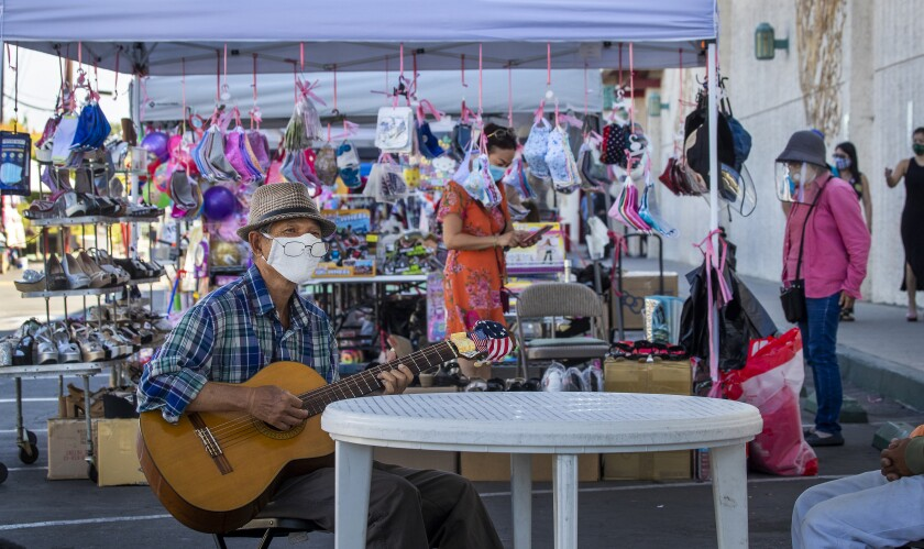 Keith Tran of Santa Ana plays a guitar while wearing a mask at the Asian Garden Mall in Westminster.