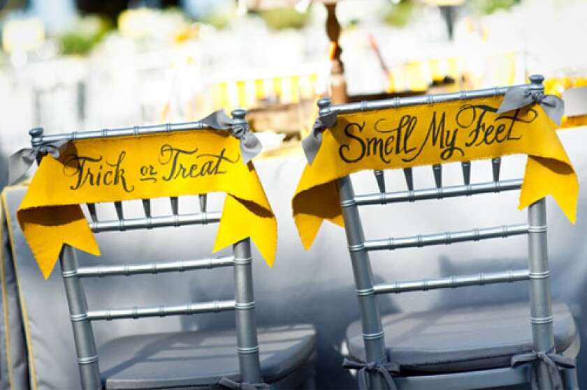 ellow canvas banners with Halloween slogans were hung on the backs of chivari chairs at a wedding designed by Calder Clark Designs.