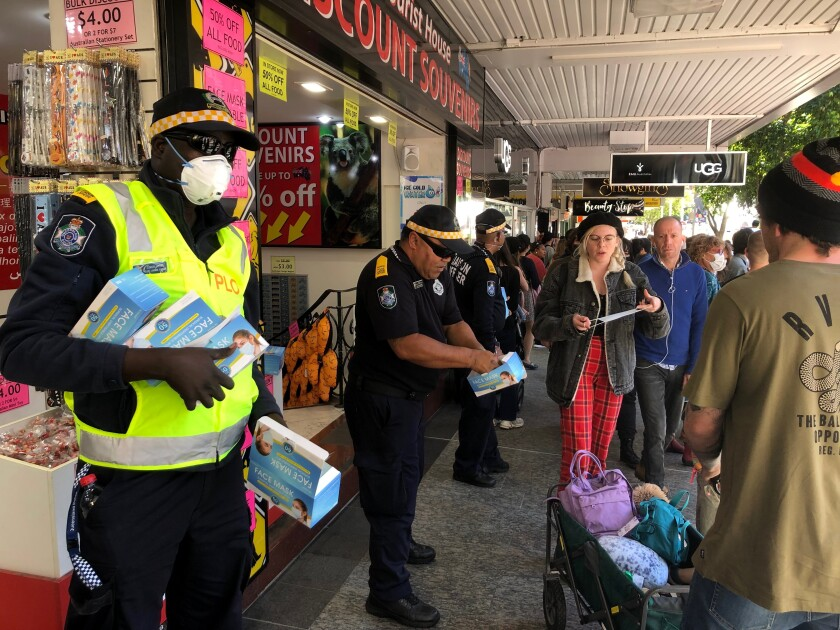 Queensland state police community liaison officers hand out face masks to people gathering for the Black Lives Matter protest in Brisbane on Saturday, June 6, 2020. Black Lives Matter protests across Australia proceeded mostly peacefully Saturday as thousands of demonstrators in state capitals honored the memory of Floyd and protested the deaths of indigenous Australians in custody. (AP Photo/John Pye)