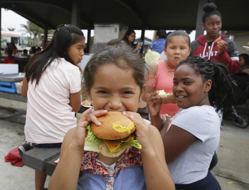 Elena Solis, 5, bites a burger at Balderrama Park at a San Diego Hunger Coalition barbeque.