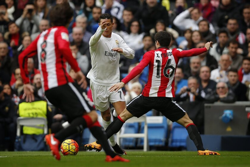 Real Madrid's Cristiano Ronaldo, center, duels for the ball with Athtletic Bilbao's Etxeita during a Spanish La Liga soccer match between Real Madrid and Athtletic Bilbao at the Santiago Bernabeu stadium in Madrid, Spain, Saturday, Feb. 13, 2016. (AP Photo/Daniel Ochoa de Olza)