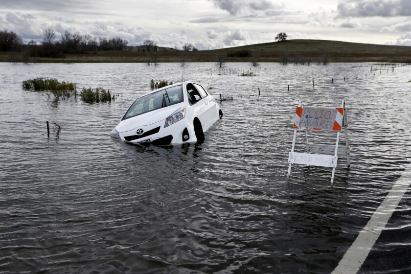 A Toyota automobile is submerged along Green Valley Road near Folsom Dam in Folsom, Calif., on Jan. 11, 2017.
