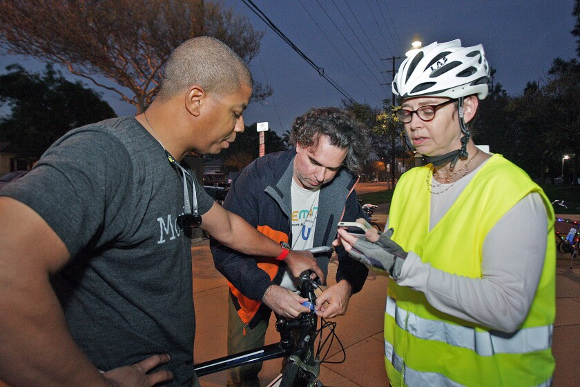 Bicyclist Christopher Black responds to survey questions posed by Mary Dickson with Walk Bike Burbank as volunteer Nicholas de Wolff attaches a bike light to the front of Black's bicycle during Operation Firefly Tuesday night.