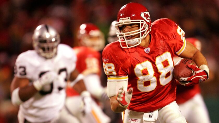 Tony Gonzalez (88) of the Kansas City Chiefs carries the ball up the field after making a catch against Oakland Raiders during the first half of the game at Arrowhead Field on December 25, 2004 in Kansas City, Missouri.