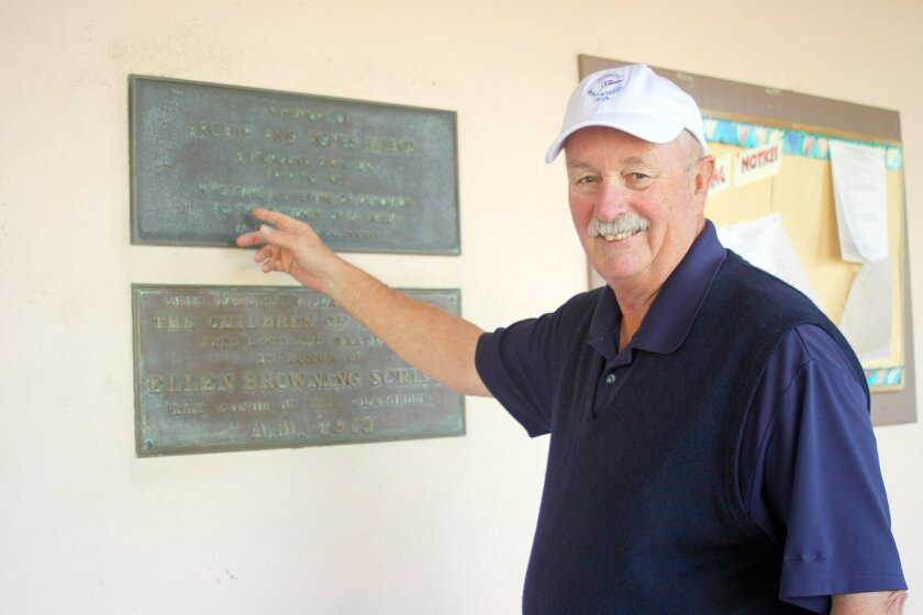 Doug Fitzgerald, President and CEO of the La Jolla Recreation Council, points to old plaques that will be restored for the centennial.