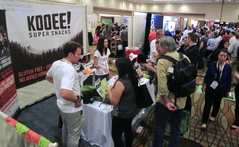 Crowds gather to see the latest at the Natural Products Expo West at the Anaheim Convention Center on Friday in Anaheim, California. People gather around the Kooee Super Snacks booth. A natural high protein snack with beef jerky dried fruit, nuts and seeds. Gluten Soy and Dairy free and Paleo Fri