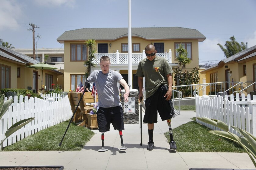 Combat injured Marine Josue Barron (right) gives advice for walking on prosthetic legs to Jason Hallett as he takes a walk for the first time outside of Freedom Station. The neat cottages in San Diego's Golden Hill neighborhood house wounded vets transitioning out of the military.