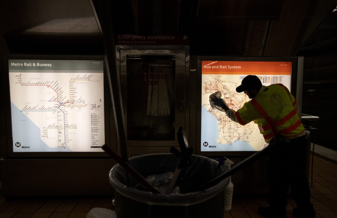 An L.A. Metro custodian cleans a transit map inside the North Hollywood station.