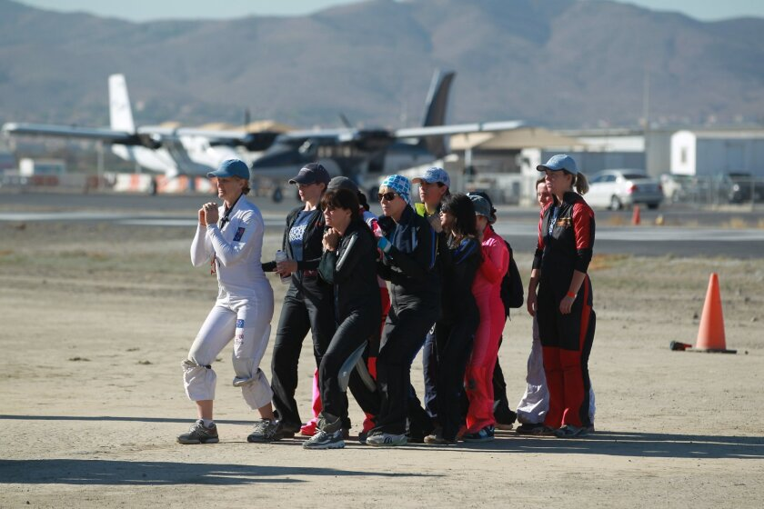 "Women skydivers from around the world do a ""dirt dive,"" practicing their aerial moves on the ground, during preparations Tuesday for their record-setting attempt at the world's largest sequential jump. They achieved the record, with 117 sky divers, on Friday, Oct. 17."