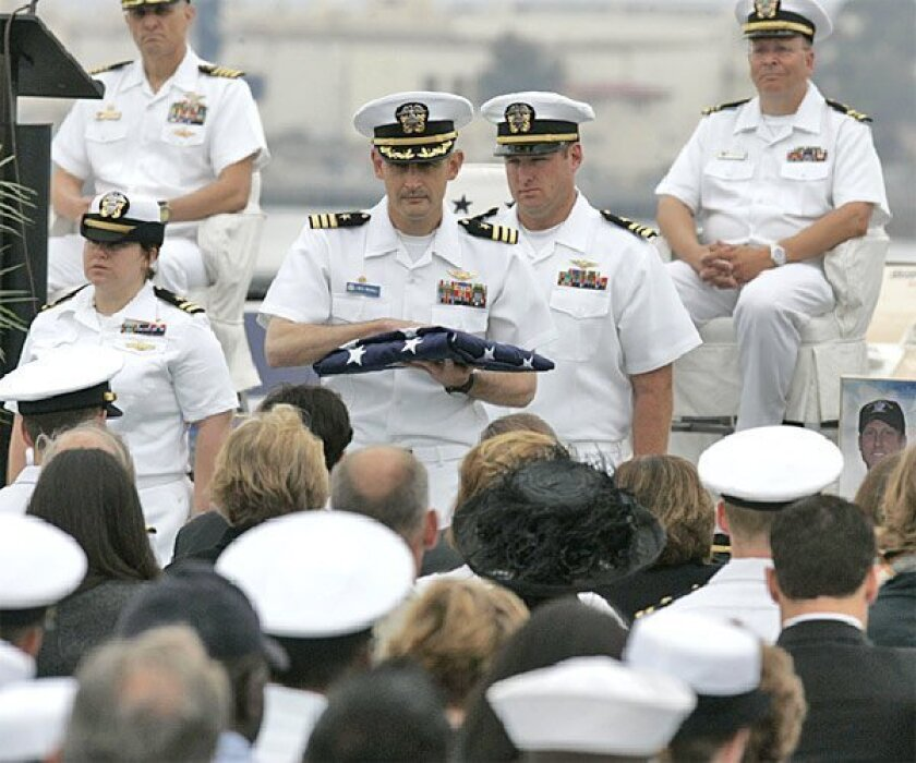 """Navy Cmdr. Wes McCall presented a flag to one of the  grieving families during a memorial service at the Midway  museum. """"We treat each other as family,"""" McCall said. (John Gibbins / Union-Tribune)"""