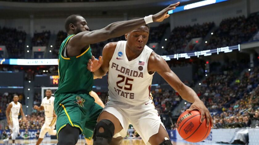 Florida State's Mfiondu Kabengele is defended by Vermont's Samuel Dingba.