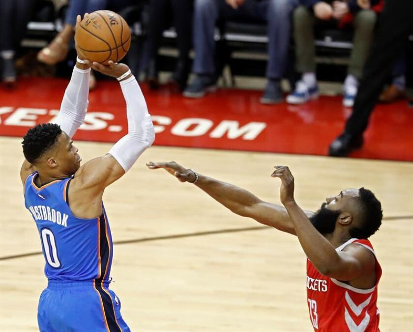 Oklahoma City Thunder player Russell Westbrook (L) takes a shot against Houston Rockets player James Harden (R) in the first half of their NBA basketball game at the Toyota Center in Houston, Texas, USA. EFE