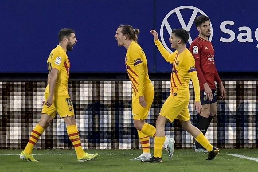 Barcelona's Jordi Alba, left, celebrates after scoring his side's first goal during the Spanish La Liga soccer match between Osasuna and FC Barcelona at El Sadar stadium in Pamplona, Spain, Saturday, March 6, 2021. (AP Photo/Alvaro Barrientos)