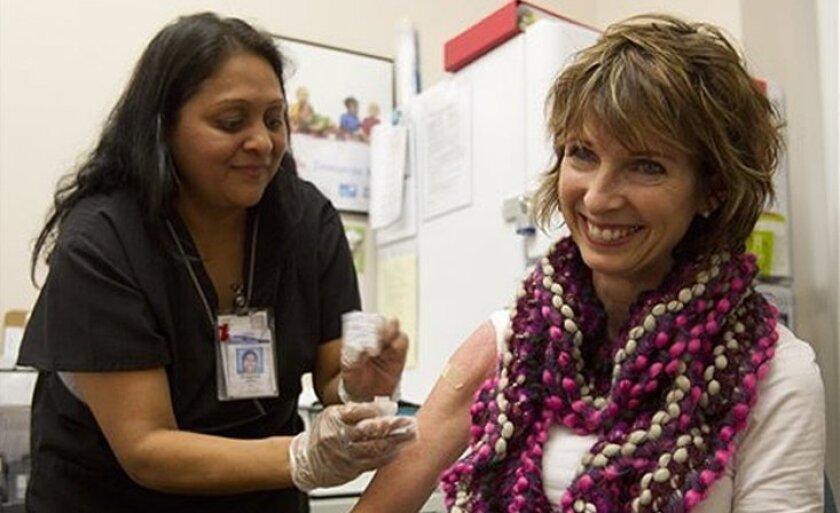 Diane Ewell, of Phoenix, right, gets a flu shot from nurse Bhagwati Bhakta at Mollen Immunization Clinics in Scottsdale, Ariz.