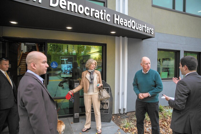 Gov. Jerry Brown with his aide Nancy McFadden outside the state Democratic Party headquarters in Sacramento.