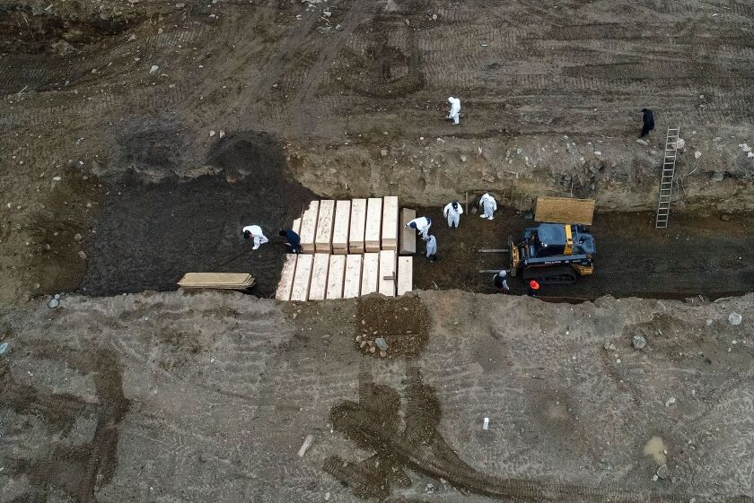 Workers wearing personal protective equipment bury bodies in a trench on Hart Island, New York City's longtime potter's field, last month.